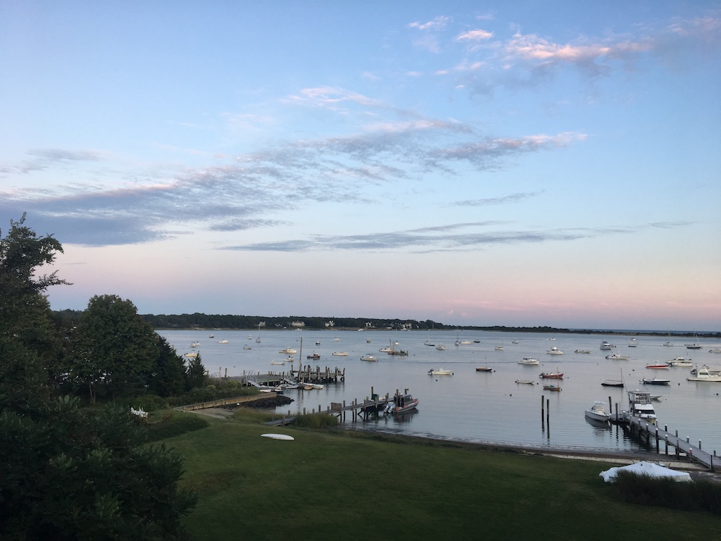 bay at sunset with bulkhead and riprap center and docks boats and soft clouds in background